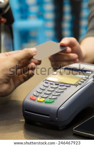 Credit Card Machine On The Table with Hand Paying by Credit Card - stock photo