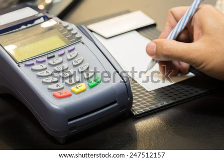 Credit Card Machine With Signing Transaction In Background - stock photo