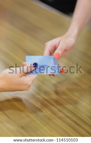 Credit card transaction between two women - stock photo