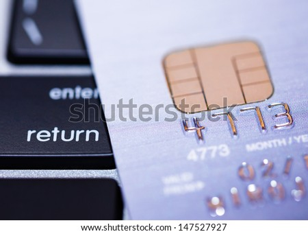 Credit cards on keyboard with microchip, e-commerce concept - stock photo