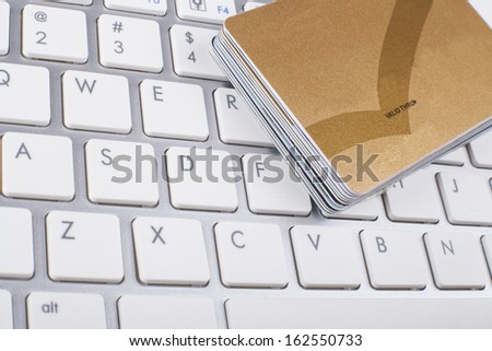 Credit cards stack on white and silver computer keyboard  - stock photo