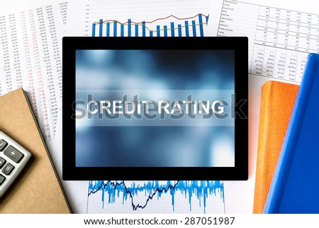 credit rating word on tablet with financial graph background - stock photo