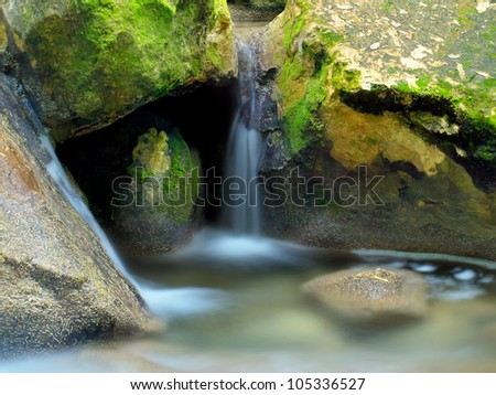 Creek and small waterfall among stones. Natural composition - stock photo