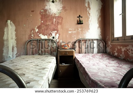 Creepy dirty and abandoned bedroom with cracked walls - stock photo