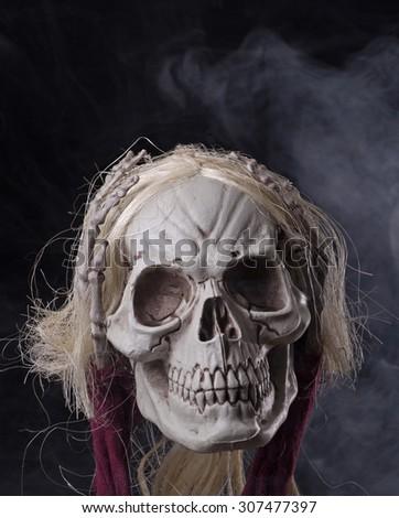 Creepy grim reaper skull on a dark smoky background - stock photo