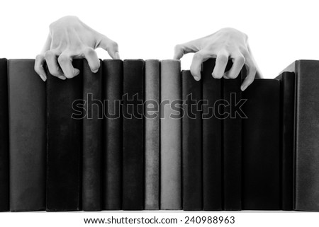creepy hands coming over books on a bookshelf - stock photo