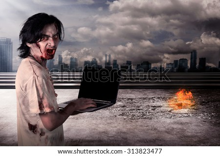 Creepy male zombie typing with laptop with city on fire background - stock photo
