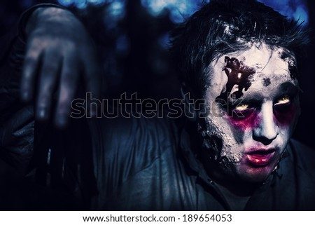 Creepy night photo of a scary zombie looking gravely ill with infectious facial wounds walking through moonlit forest. Attack of the killer monsters - stock photo