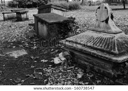 Creepy old derelict overgrown graveyard with tombs sunk and broken graves - stock photo