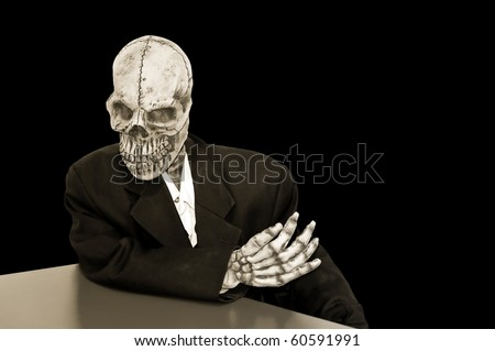 creepy skeleton in a dusty suit on a black background - stock photo