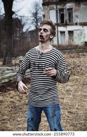 Creepy zombie sailor walking in abandoned village - stock photo