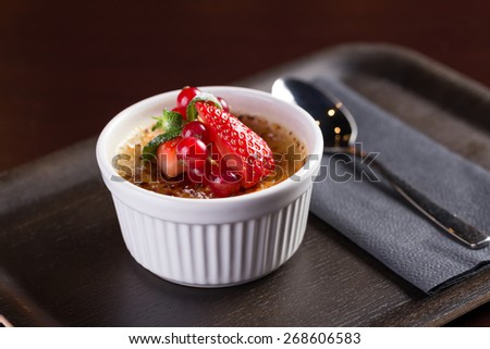 Creme brulee dessert with strawberry isolated on black background - stock photo