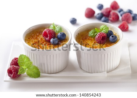 Creme brulee.French vanilla cream dessert with caramelised sugar and berries on top. - stock photo