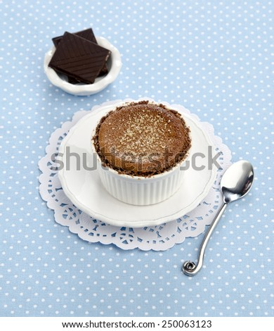 Creme brulee with dark chocolate on a white saucer on a blue background - stock photo