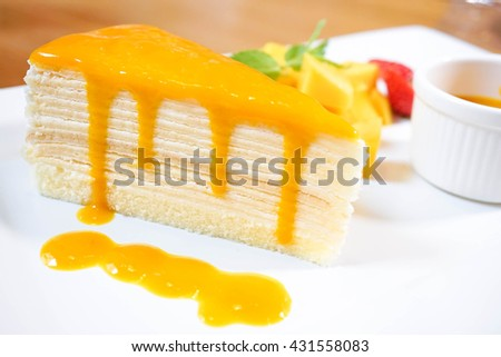 Crepe cake bakery piece with Mango sauce on the top. Mango Crepe Cake or Mango Layer Cake Dessert. Served with fresh Mango and strawberry. - stock photo