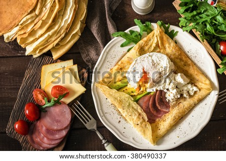 Crepe galette with ham, avocado, soft white cheese and poached egg on white plate. Sliced yellow cheese, pastrami, cherry tomatoes, green salad and stack of crepes on side. Top view - stock photo