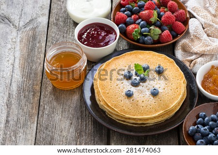 crepes, fresh berries and jam on a wooden background, top view - stock photo