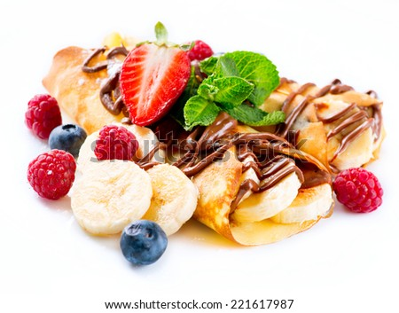 Crepes With Banana, Chocolate and Berries. Pancakes isolated on a white background - stock photo