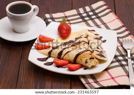 Crepes with Banana, Chocolate and strawberries with cup of coffee - stock photo
