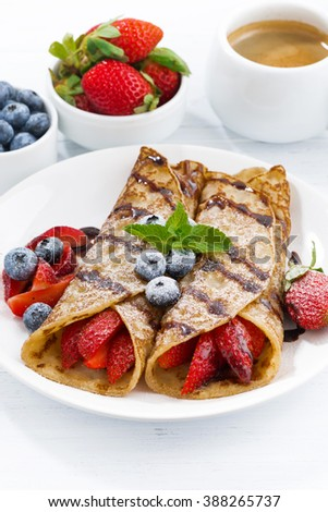 crepes with berries and chocolate sauce for breakfast on plate, vertical, closeup - stock photo