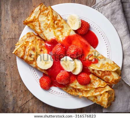 Crepes with strawberries and banana on wooden table, top view - stock ...