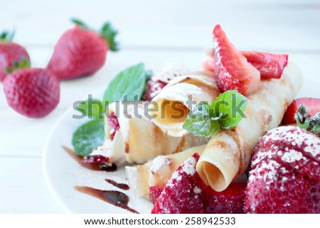 Crepes with strawberry fruits and chocolate topping - stock photo