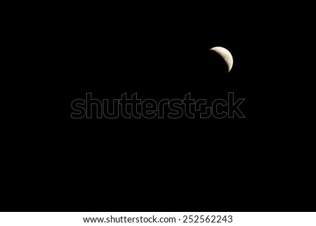 crescent moon against a black sky - stock photo