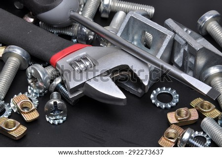 Crescent wrench screws and bolts on black metal surface - stock photo