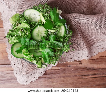 Cress salad with sliced cucumber and parsley in glass bowl on rustic wooden table background - stock photo