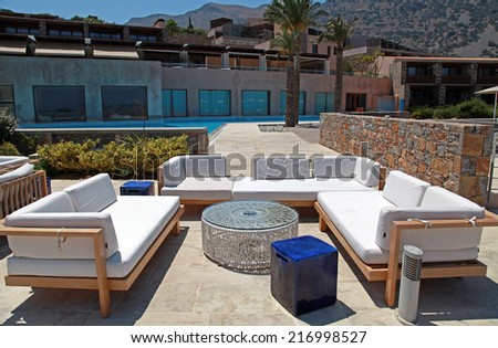 CRETE, GREECE - JULY 14, 2012: outdoor furniture on beautiful mediterranean patio in summer resort, Crete, Greece, wide angle image - stock photo