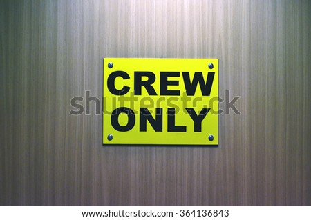 CREW ONLY - yellow sign on the door - stock photo