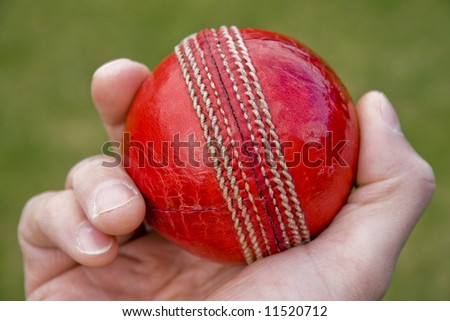 Cricket bowlers hand with ball about to bowl - stock photo