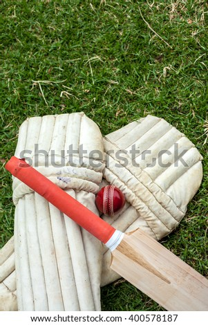 Cricket Equipment at cricket field,showcasing bats, balls, helmets and pads - stock photo