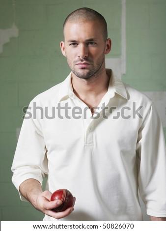 Cricket player holding ball, portrait - stock photo