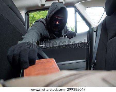 Crime concept. Burglar taking wallet from car. - stock photo