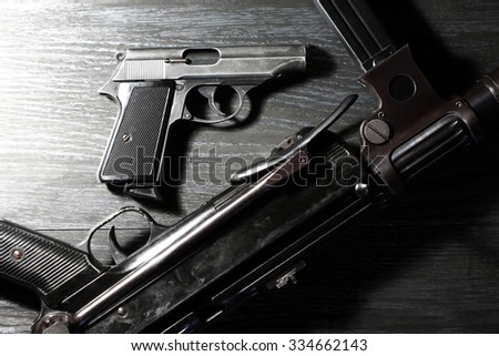 Crime concept. Pistols and submachine gun on dark background under beam of light - stock photo