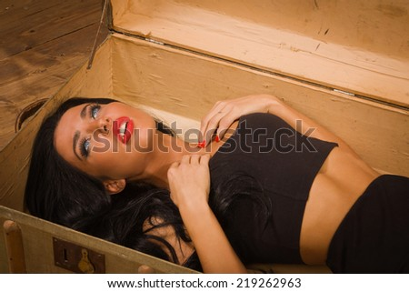 Crime scene in a vintage style. Pretty victim lying in the suit-case - stock photo