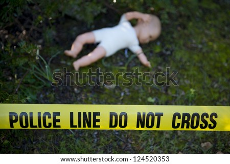 Crime scene in the forest: Yellow police line do not cross tape and doll - stock photo