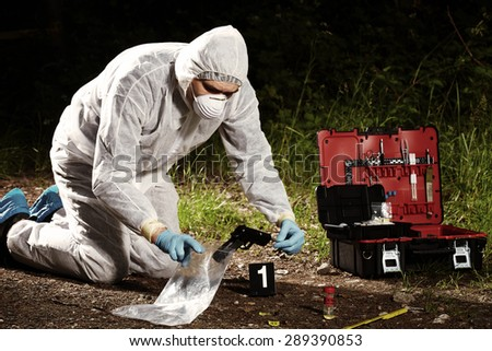 Crime scene investigation - collecting pistol and cartridges by technician - stock photo