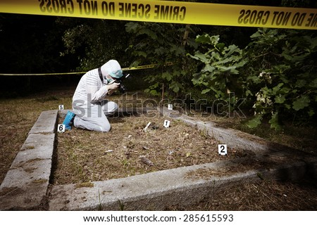 Crime scene investigation - police photographer at work - stock photo
