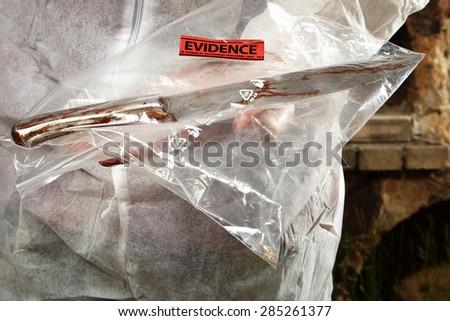 Crime scene investigation - technician holds evidence - stock photo