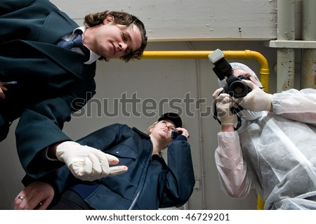 Crime scene investigations team hovering over my dead body. A police inspector, wearing rubber gloves, a policewoman using her radio, and forensic expert taking pictures as evidence - stock photo