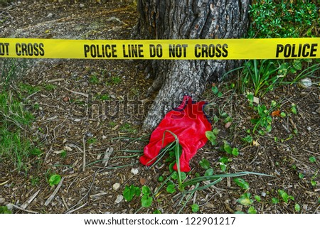 Crime scene: Police line do not cross tape and romper suit as evidence - stock photo