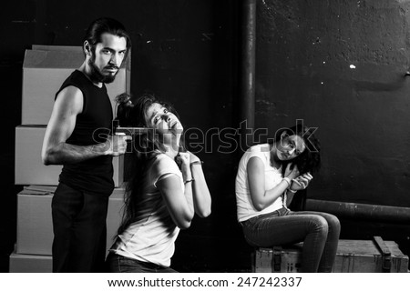 Crime. Two beautiful girls kidnapped by criminals. Terrorist is threatening hostages with a gun. - stock photo