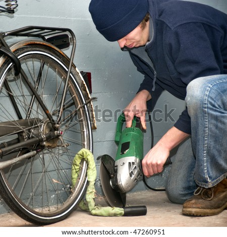 Criminal grinding through the lock of a stolen bicycle - stock photo