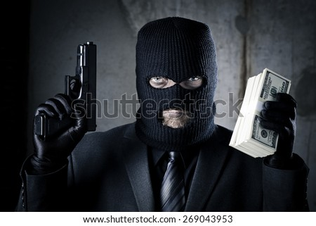 Criminal holding gun and stack of money - stock photo