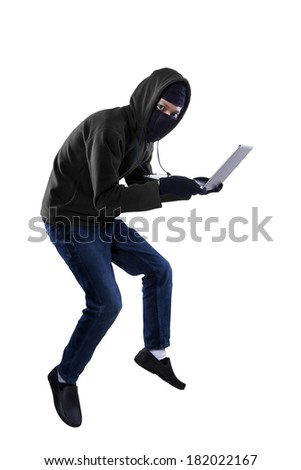 Criminal in dark clothes and balaclava is stealing a laptop computer - stock photo