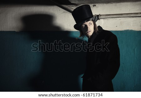 Criminal man in vintage black coat and top hat in the dark interior. Natural darkness and colors - stock photo