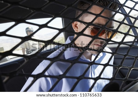 Criminal sitting in police car - stock photo