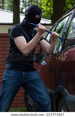 Criminal smashing a glass and breaking into a car - stock photo